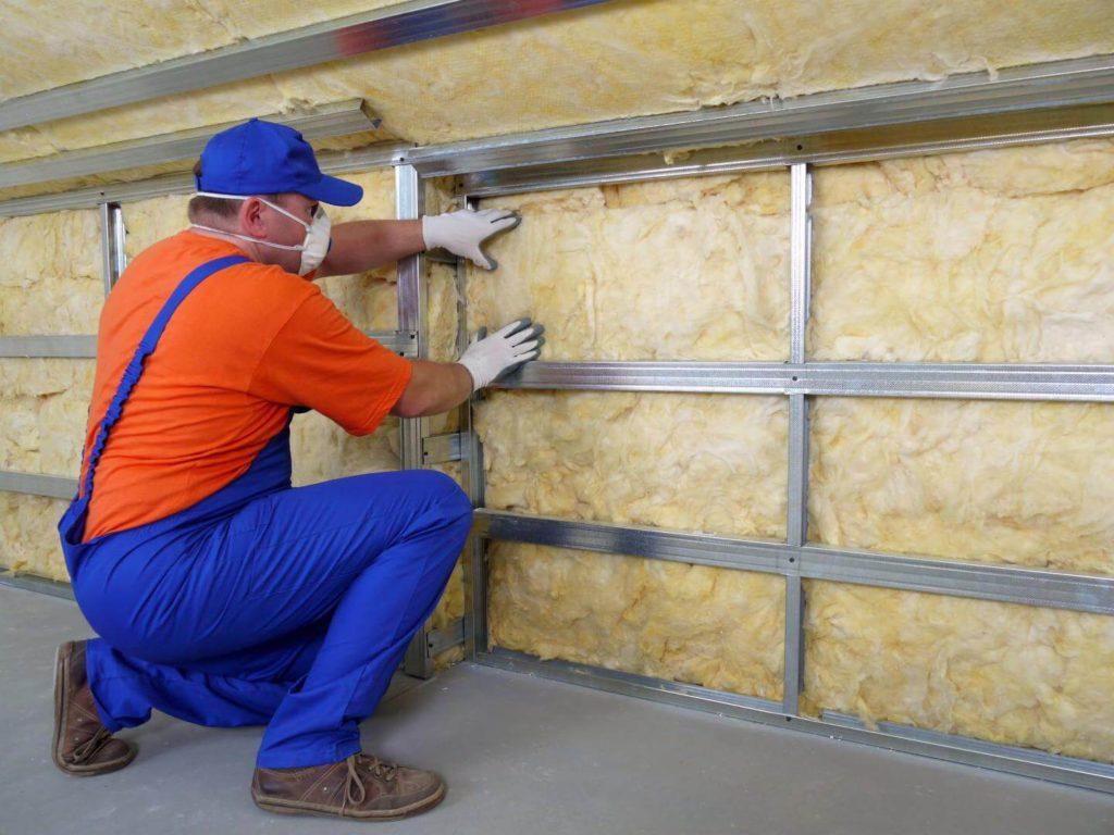 Technicien procédant à une isolation des murs par l'intérieur