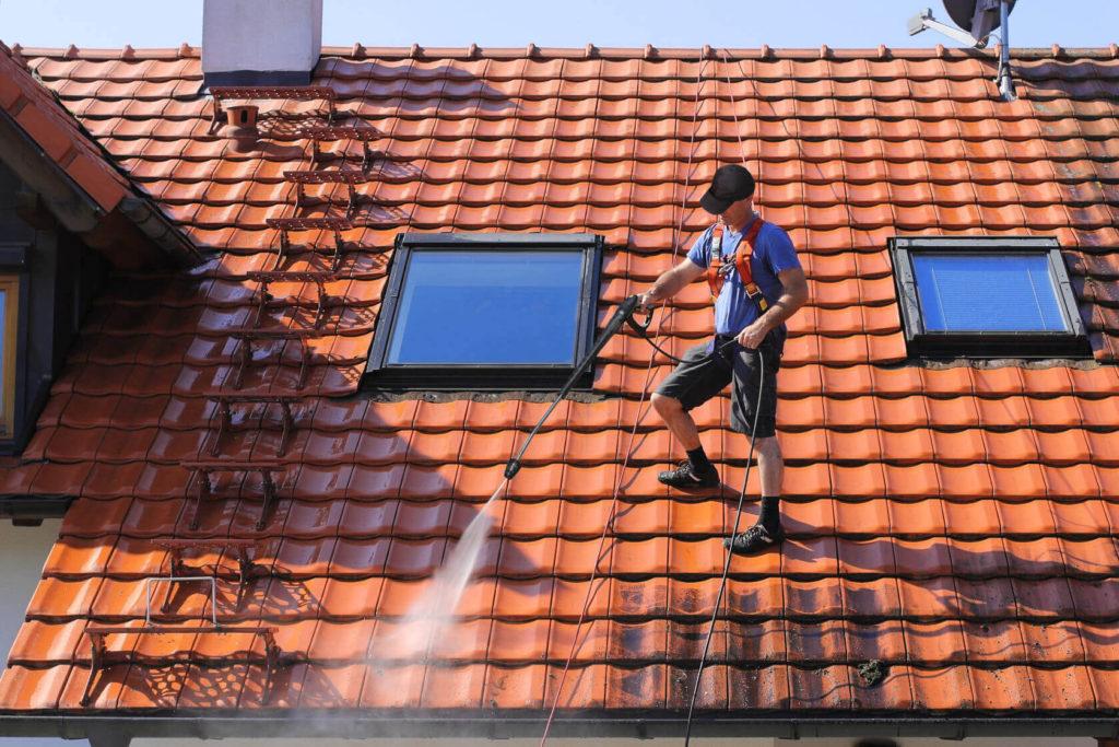 Entretien de toiture : opération de nettoyage d'un toit en tuiles
