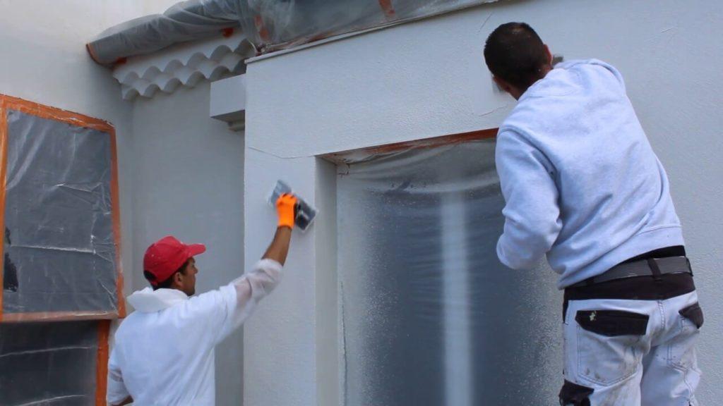 Professionnels effectuant la fintion d'une isoaltion par l'extérieur à l'aide d'une enduit