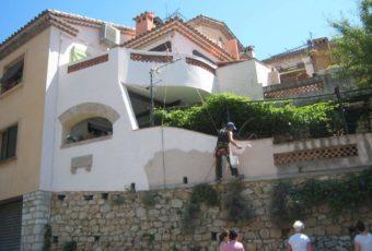 Techniciens traitant la façade d'une villa