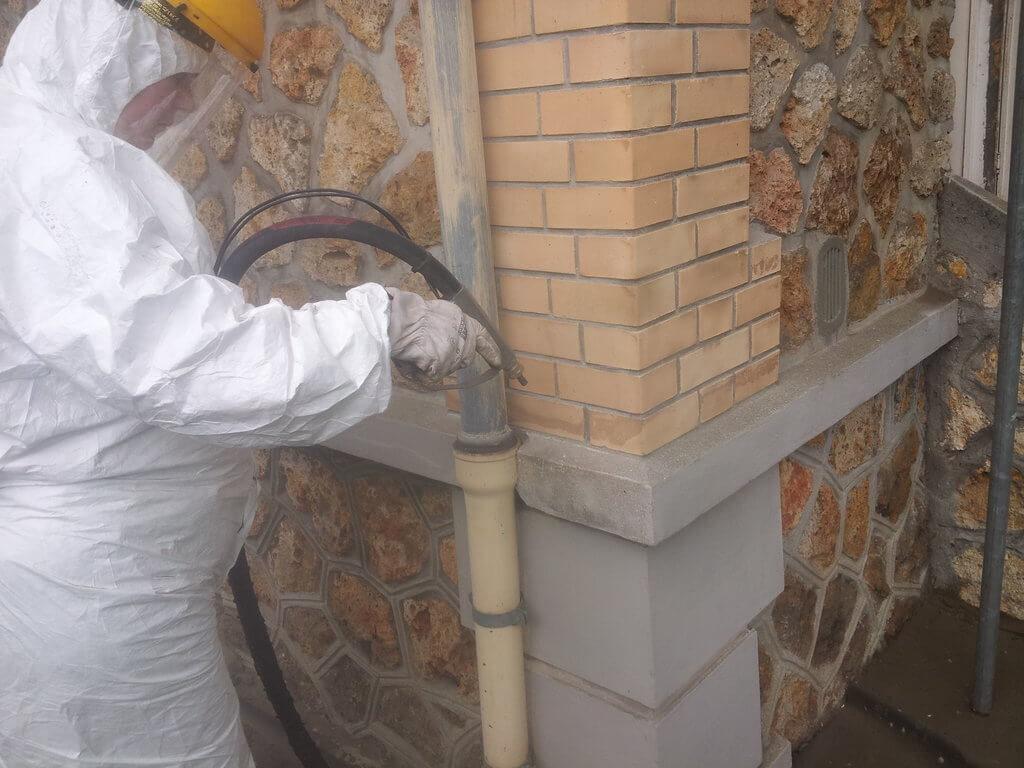 Technicien procédant à un aérogommage de façde