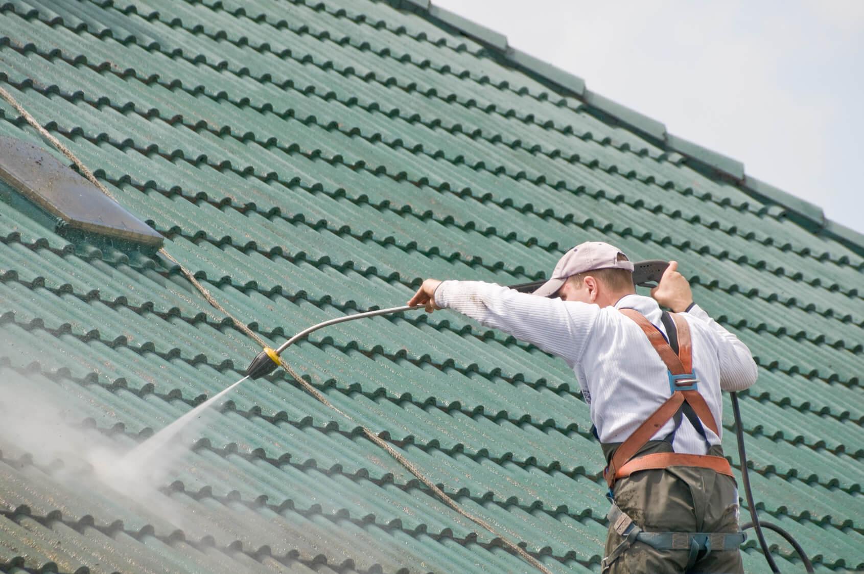 Technicien démoussant une toiture