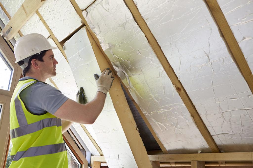 Technicien procédant à l'isolation d'une toiture par l'intérieur