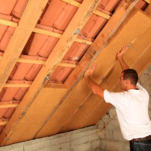Artisan procédant à la pose d'une isolation de toiture par l'intérieur