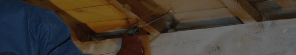 Professionnel procédant à un traitement de charpente bois contre les insectes xylophages