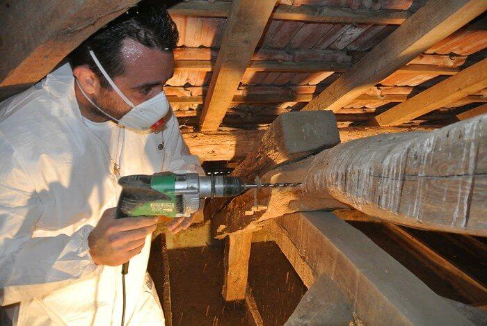 Technicien procédant à un traitement de charpente bois