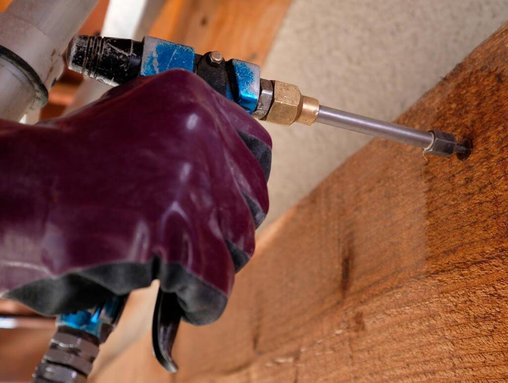 Technicien procvédant à l'application d'un traitement préventif de charpente
