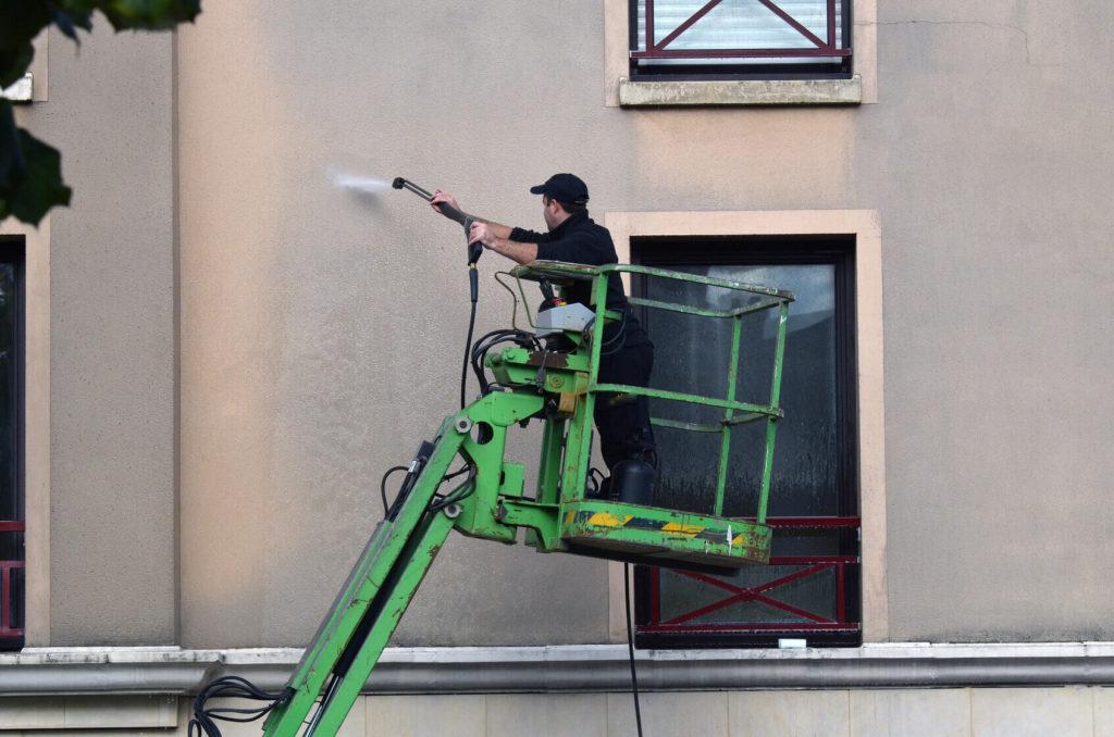 Technicien procédant à des travaux de ravalement de façade en rénovation à Lyon